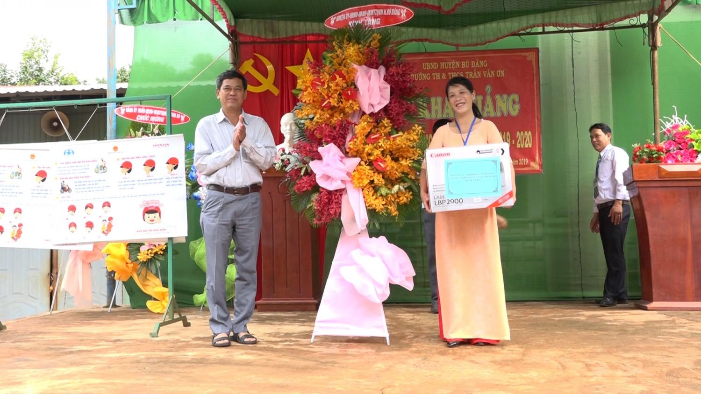 Bí thư huyện ủy Huỳnh Hữu Thiết tặng hoa và quà chúc mừng tại lễ khai giảng